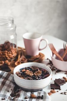 건강한 아침 식사. 초콜릿 그래놀라 스무디와 커피 한 잔. 접시에 아몬드, 딸기, 요구르트. 성분. 에코, 비건