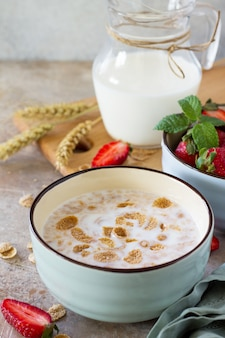 石の背景に健康的な朝食のクローズアップ全粒フレークミルクと新鮮なイチゴ