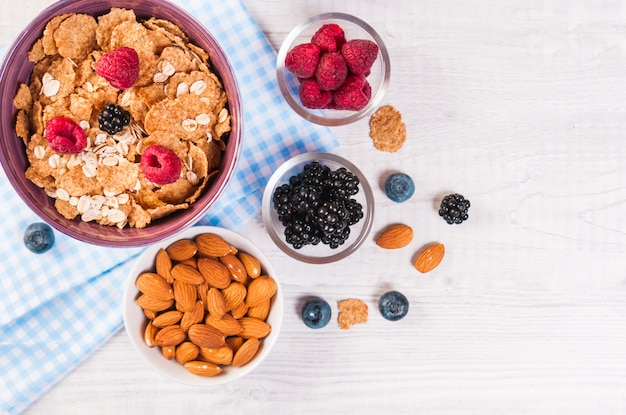 Healthy breakfast, coffee cornflakes berries and milk, with text space top view close-up