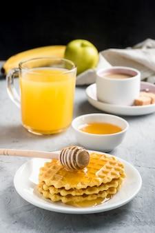Healthy breakfast coffee juice cookies honey banana on grey