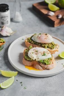 健康的な朝食のコンセプトです。アボカドワカモレとポーチドエッグ、ニンニク、ライムを添えた全粒パンのトースト。健康的な生活様式。
