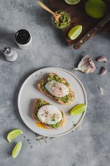 健康的な朝食のコンセプトです。アボカドワカモレとポーチドエッグ、ニンニク、ライムを添えた全粒パンのトースト。家庭料理の食材。