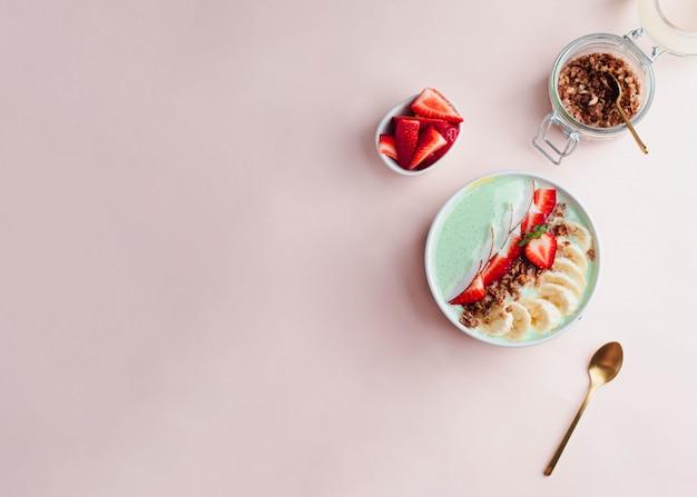健康的な朝食のコンセプトです。ピンクの背景にイチゴ、バナナ、ミントヨーグルトと全粒グラノーラボウル。プロバイオティクスの概念。 copyspace付きフラットレイ