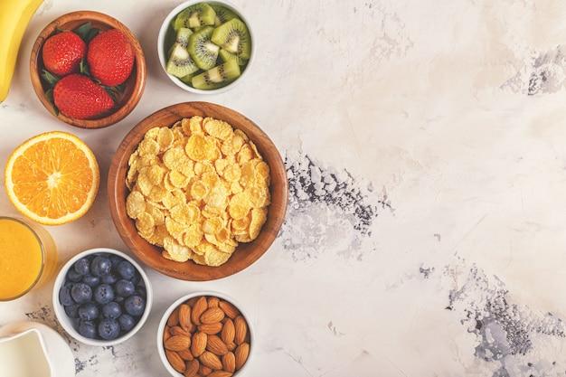 コーンフレーク、ベリー、ナッツのボウルで健康的な朝食のコンセプト