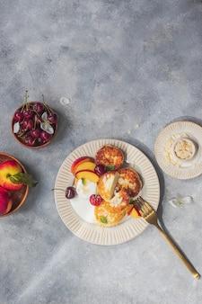 커피와 함께 건강한 아침 식사 개념입니다. 체리, 천도 복숭아, 꿀, 그리스식 요구르트, 민트를 곁들인 치즈 팬케이크