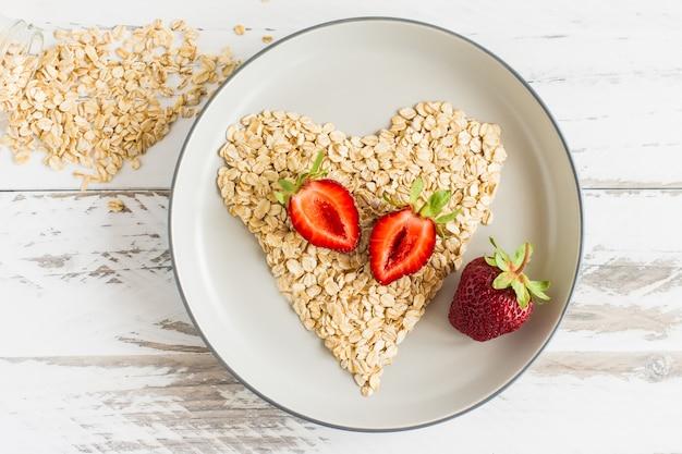心のshaoeのイチゴとオーツ麦フレークと健康的な朝食のコンセプト:プレートのクローズアップのイチゴとフレーク。上面図。