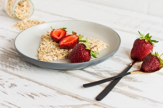 心のshaoeのイチゴとオーツ麦フレークと健康的な朝食のコンセプト:プレートのクローズアップのイチゴとフレーク。