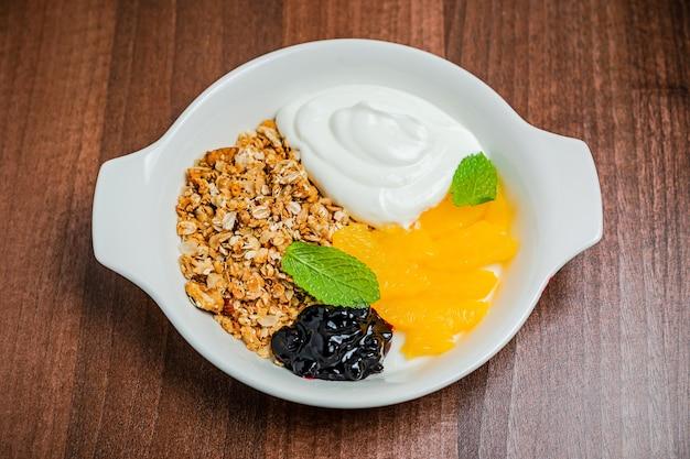 Здоровый завтрак, состоящий из мюсли с греческим йогуртом и свежего апельсина