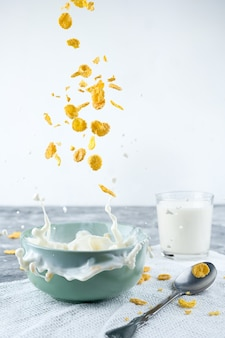 파란색 배경에 건강한 아침 식사-콘플레이크와 우유 스플래시.