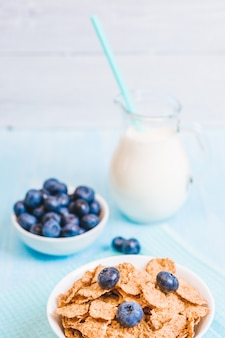 Healthy breakfast, cornflakes blueberry and milk, nuts, almond with text space close-up