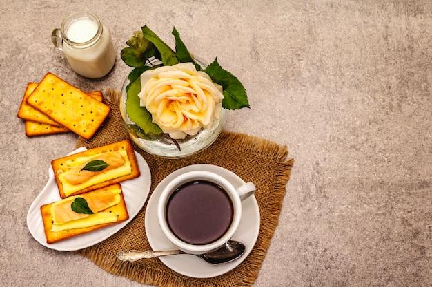 Здоровый завтрак. чашка кофе (черный чай), молоко, крекеры с маслом и лососем