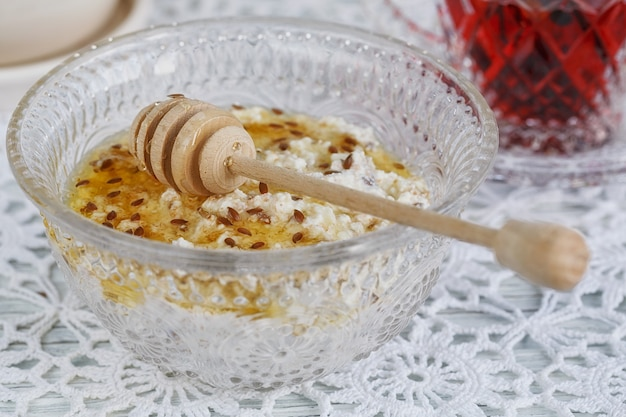 Здоровый завтрак. чашка красного чая каркаде, творог с овсяными хлопьями, льняное семя и мед.