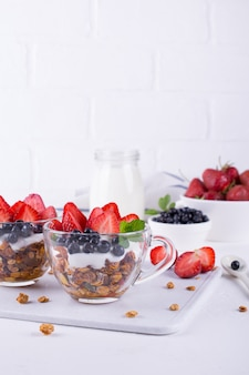 Healthy breakfast in a cup with homemade baked granola, fresh berries, and yogurt on a white table background