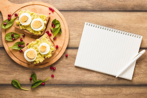 Healthy breakfast on cutting board with blank spiral book and pen over wooden background