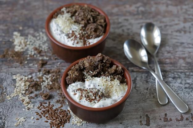 Healthy breakfast or dessert with greek yogurt, chocolate granola and seeds. keto diet.
