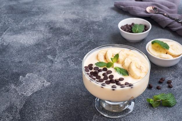 ヘルシーな朝食、プレートにミルクヨーグルトバナナとチョコレートを添えたデザート。暗いコンクリートの背景。コピースペース。