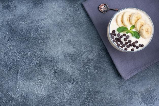 ヘルシーな朝食、プレートにミルクヨーグルトバナナとチョコレートを添えたデザート。暗いコンクリートの背景。上面図、コピースペース。