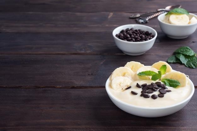 ヘルシーな朝食、プレートにミルクヨーグルトバナナとチョコレートを添えたデザート。暗い木の背景。コピースペース。