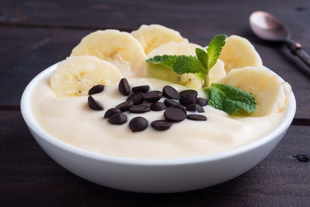 Healthy breakfast, dessert with milk yogurt banana and chocolate on a plate. dark wooden.