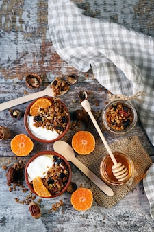Healthy breakfast or dessert. yogurt with granola and tangerine. homemade granola. honey. flat lay.
