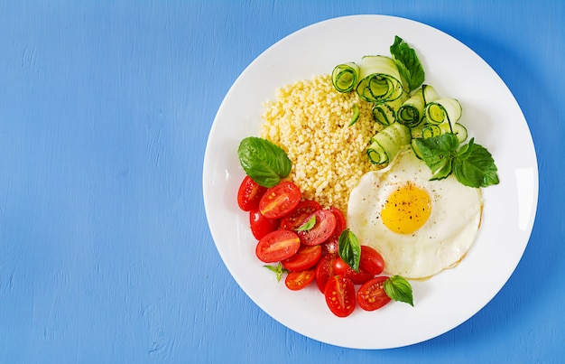건강한 아침 식사. 식이 메뉴. 기장 죽과 토마토, 오이 샐러드와 달걀 프라이.