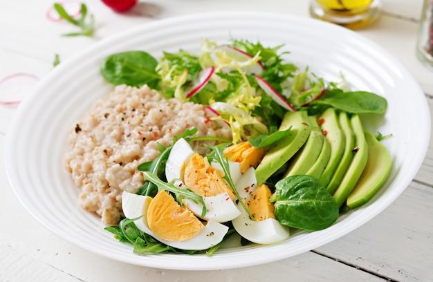 健康的な朝食。食事メニュー。オートミールのおridgeとアボカドのサラダと卵。