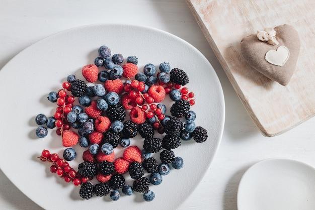 新鮮な生のベリーの果実を混ぜて食べる健康的な朝食