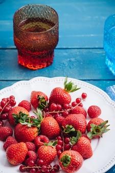 新鮮な赤いベリーの果実のミックスを食べる健康的な朝食