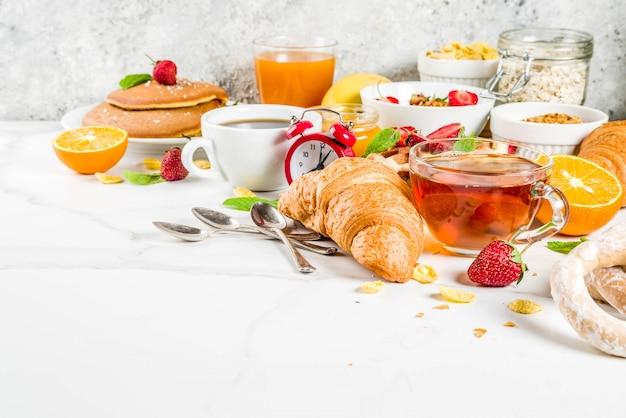 ヘルシーな朝食のコンセプト、さまざまなモーニングフード-パンケーキ、ワッフル、クロワッサンオートミールサンドイッチ、グラノーラ、ヨーグルト、フルーツ、ベリー、コーヒー、紅茶、オレンジジュース