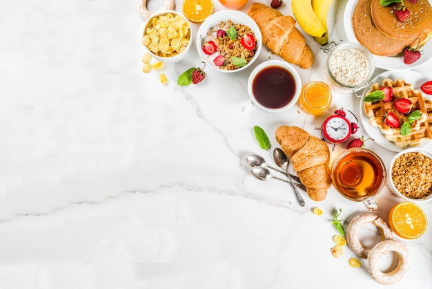 Healthy breakfast eating concept, various morning food - pancakes, waffles, croissant oatmeal sandwich and granola with yogurt, fruit, berries, coffee, tea, orange juice, white background Premium Photo