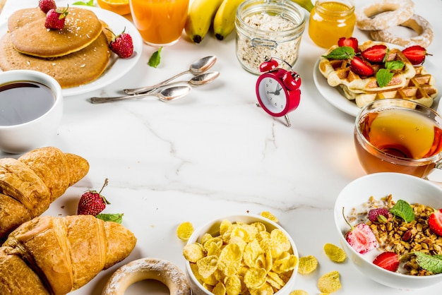 Healthy breakfast eating concept various morning food - pancakes waffles croissant oatmeal sandwich and granola with yogurt fruit berries coffee tea orange juice white background
