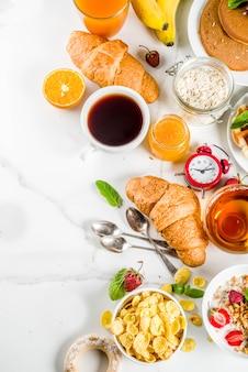 Healthy breakfast eating concept, various morning food - pancakes, waffles, croissant oatmeal sandwich and granola with yogurt, fruit, berries, coffee, tea, orange juice