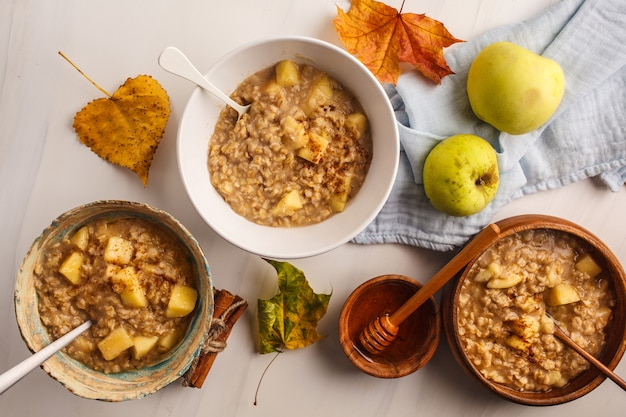 Healthy breakfast flat lay. autumn apple oatmeal with cinnamon and honey.
