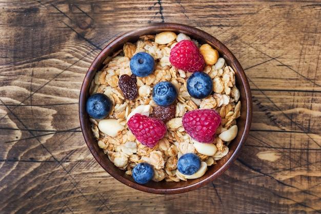 健康的な朝食。新鮮なグラノーラ、ミューズリー、ヨーグルト、ベリー、木製テーブルを配しております。コピースペース。