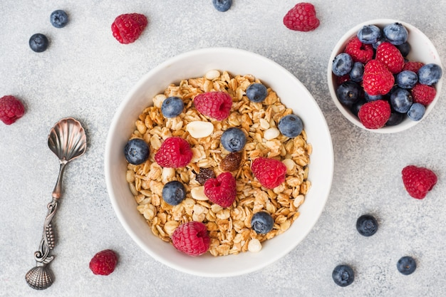 Healthy breakfast. fresh granola, muesli with yogurt and berries on grey background. copy space