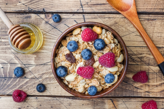 Healthy breakfast. fresh granola, muesli with yogurt and berries on wooden surface
