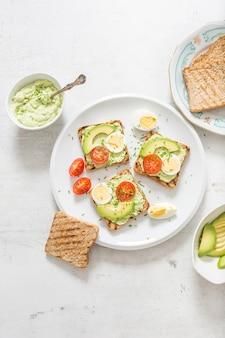 아보카도 스프레드 과카몰리 달걀 토마토와 골파를 곁들인 토스트의 건강한 아침 식사.