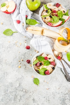 Healthy  breakfast, fruit and berry salad with spinach, granola, apple and banana