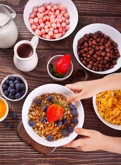 健康的な朝食。グラノーラ、新鮮なベリーのミューズリー。子供の手はボウルを取ります。