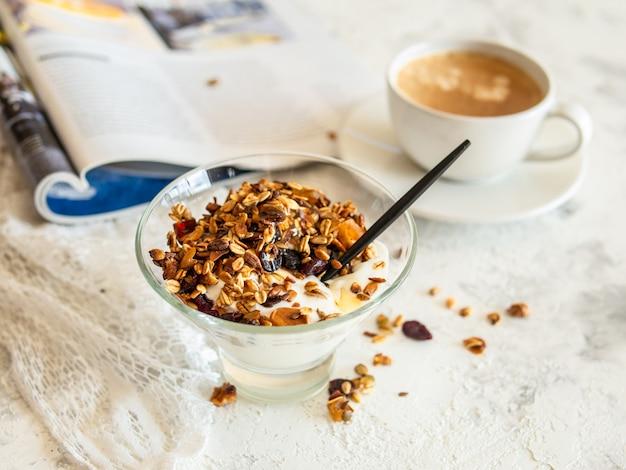 健康的な朝食。グラノーラ、ミューズリー、カボチャの種、蜂蜜、ヨーグルト、ガラスのボウル