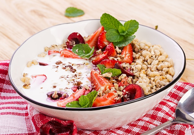 Здоровый завтрак - мюсли, клубника, вишня, орехи и йогурт в миску на деревянном столе. вегетарианская концепция еды.