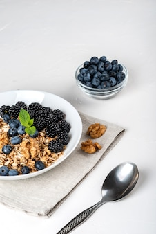 Healthy breakfast. homemade granola, muesli, cereals with blackberries, blueberries, nuts, honey and mint in a white bowl