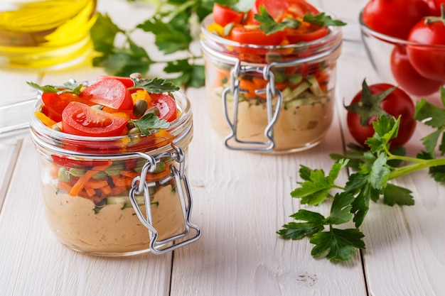 Healthy breakfast - hummus with vegetables in glass jars.