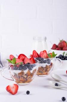 Здоровый завтрак в чашке с домашней запеченной мюсли, свежими ягодами и йогуртом на белом фоне стола
