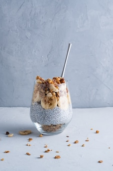 바나나 호두 치오 씨앗 요구르트와 뮤즐리를 곁들인 유리잔에 담긴 건강한 아침 식사