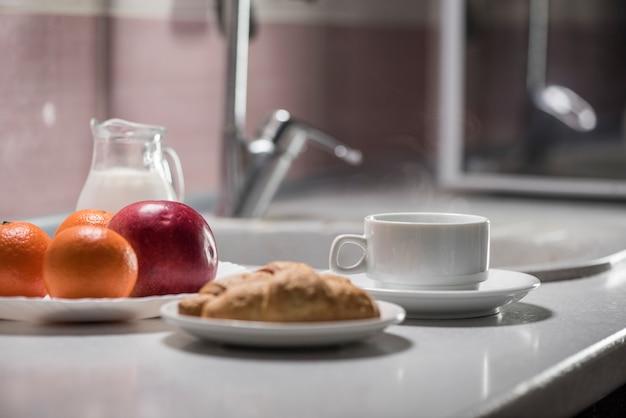 Здоровый завтрак на кухне с кофе, круассанами, молоком и фруктами