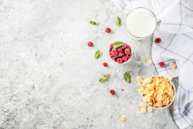 健康的な朝食の食材。朝食シリアルフレークミルクまたはヨーグルトガラスラズベリーと灰色の石の背景にミント