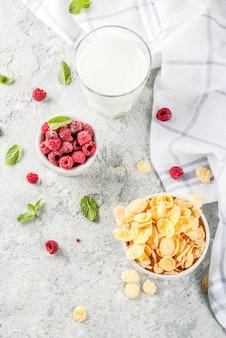 Healthy breakfast ingredients. breakfast cereal flakes milk or yogurt glass raspberries and mint on grey stone background