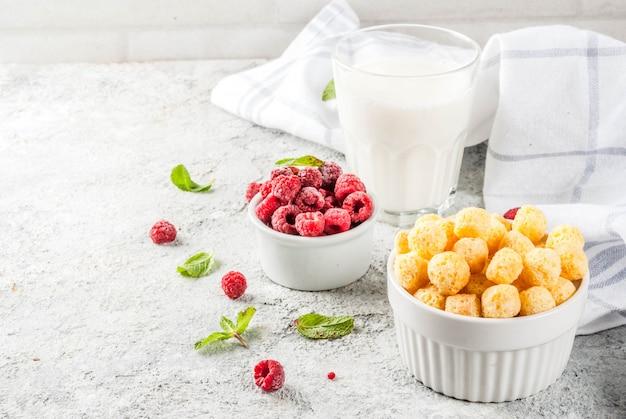 健康的な朝食の食材。朝食用シリアル、ミルクまたはヨーグルトのグラス、ラズベリー、ミント、灰色の石背景、コピースペース