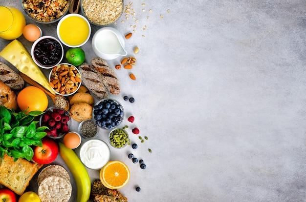 Healthy breakfast ingredients, food frame. granola, egg, nuts, fruits, berries, toast, milk